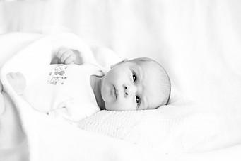 Newborn baby in a white vest on a white background