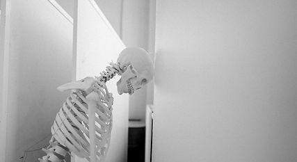 Skeleton leaning against wall