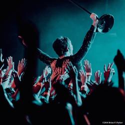 artist crowd surfing at concert