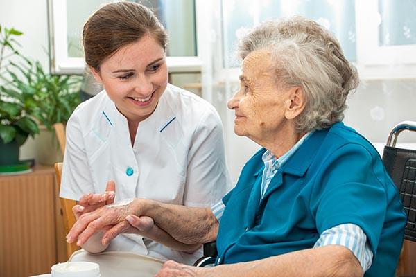 Caregiver managing psoriasis in elderly patient