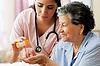 caregiver assisting senior with her medication