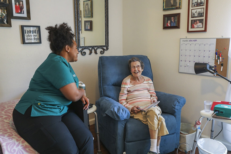 female caregiver sitting on bed smiling at female senior sitting in chair reading
