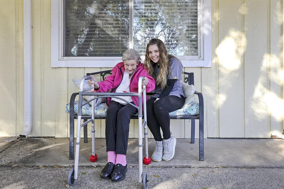 Female Caregiver sitting on bench outside with female senior