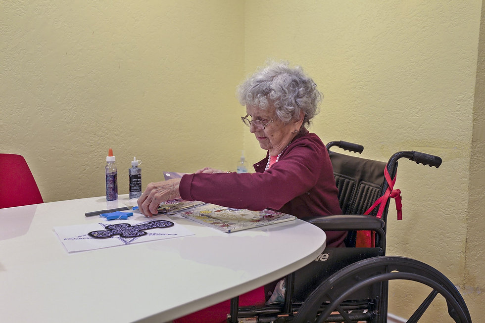 Female senior doing an art project at kitchen table