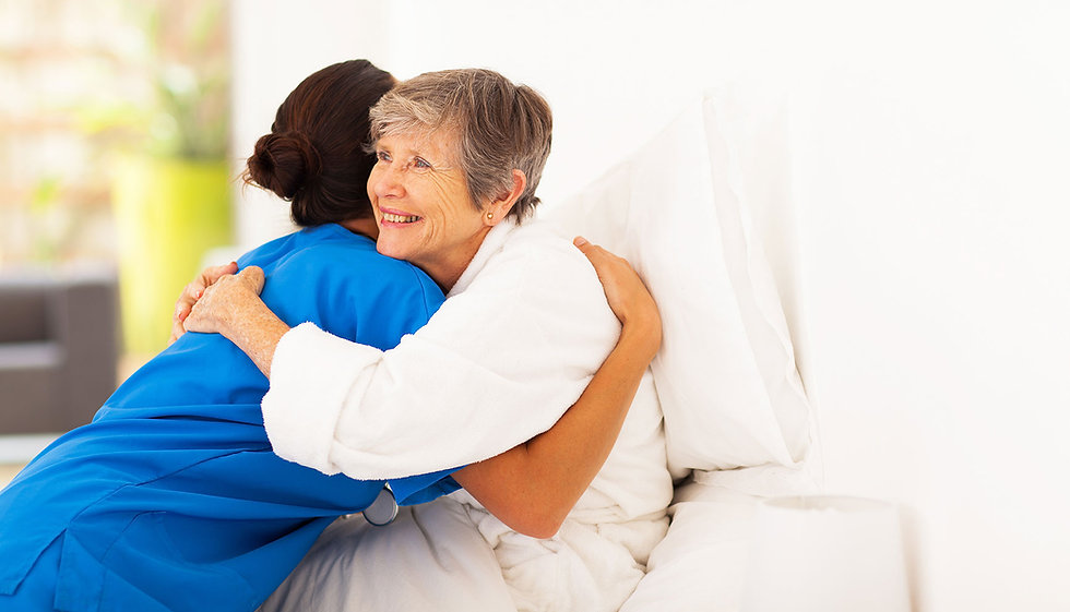 caretaker hugging female senior sitting in bed