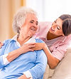 female senior sitting on couch looking to her left smiling at caretaker behind her