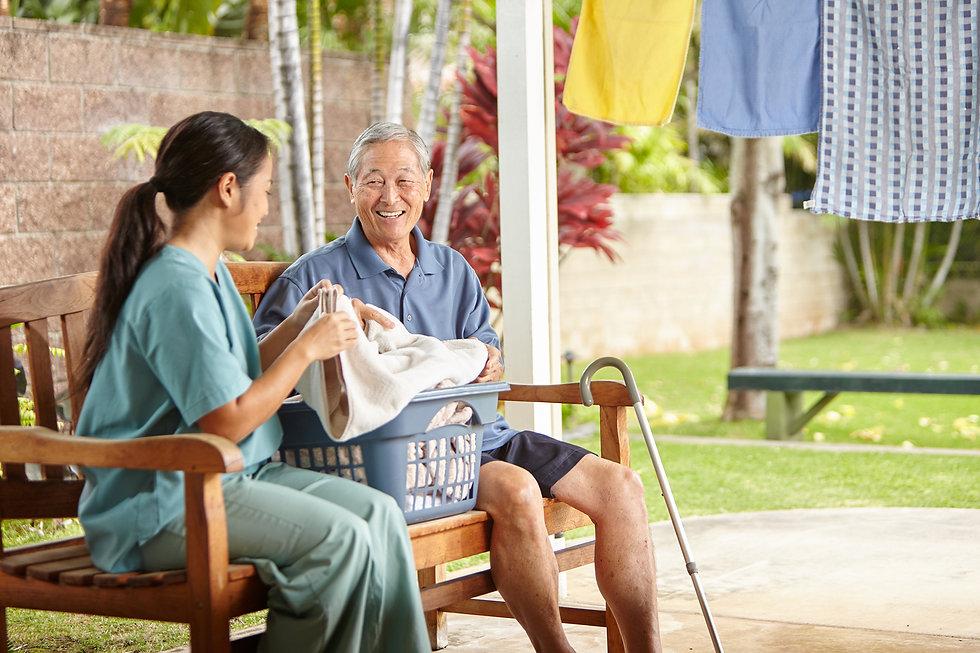 caretaker performing homemaker services, caretaker folding laundry