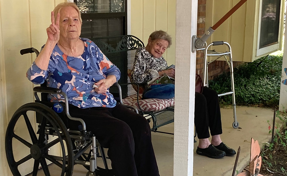 female seniors sitting outside on the front patio on a sunny day