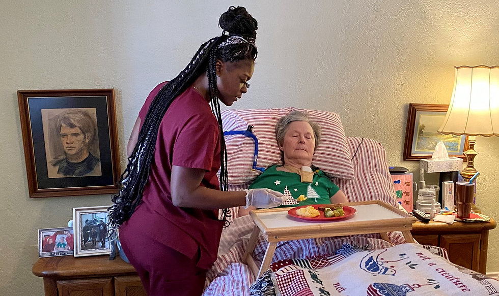 Female caregiver helping female bedbound senior eat