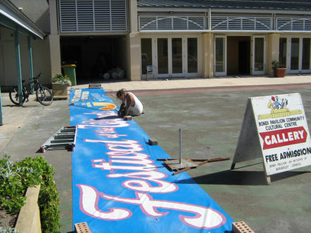 Artist Steve Smith painting the 30th year banner. Every year a different banner was painted and hung on the Pavilion.