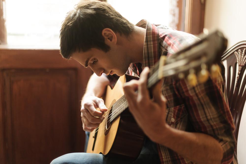 Young man practicing guitar