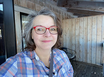 A photo of a woman with grey hair and red glasses, smiling