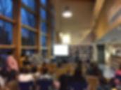 Persona dando charla en una biblioteca con mucha gent