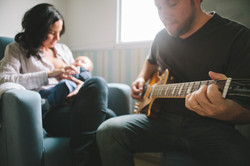 ensaio de familia em casa mãe amamentando pai tocanod violão