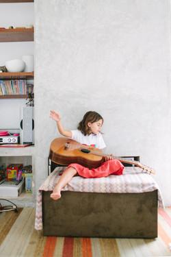 ensaio de familia em casa menina toca violão