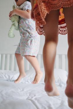 ensaio de familia em casa crianças pulanod na cama