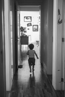 ensaio de familia em casa menio correndo no corredor