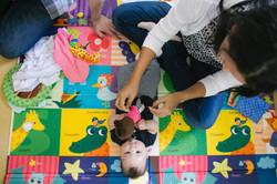 ensaio de familia em casa mãe brinca com bebê