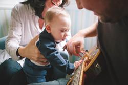 ensaio de familia em casa bebê tocando violão