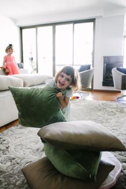 ensaio de familia em casa menina brincando na almofada