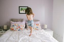 ensaio de familia em casa menina pula na cama