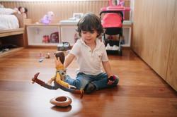 ensaio de familia em casa menino brincando woody toy story