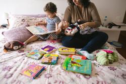 ensaio de familia em casa mãe e filhos lendo juntos