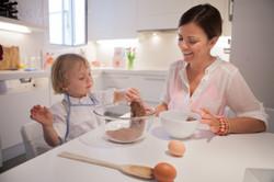 ensaio de familia em casa mãe e filho fazendo bolo