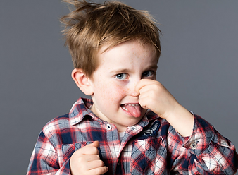 A young boy holds his nose and sticks out his tounge in disguiste