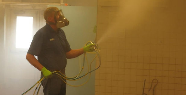 Technician spraying a fog onto ceilings and walls of a room.