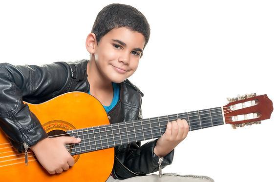 Cute hispanic boy playing an acoustic gu