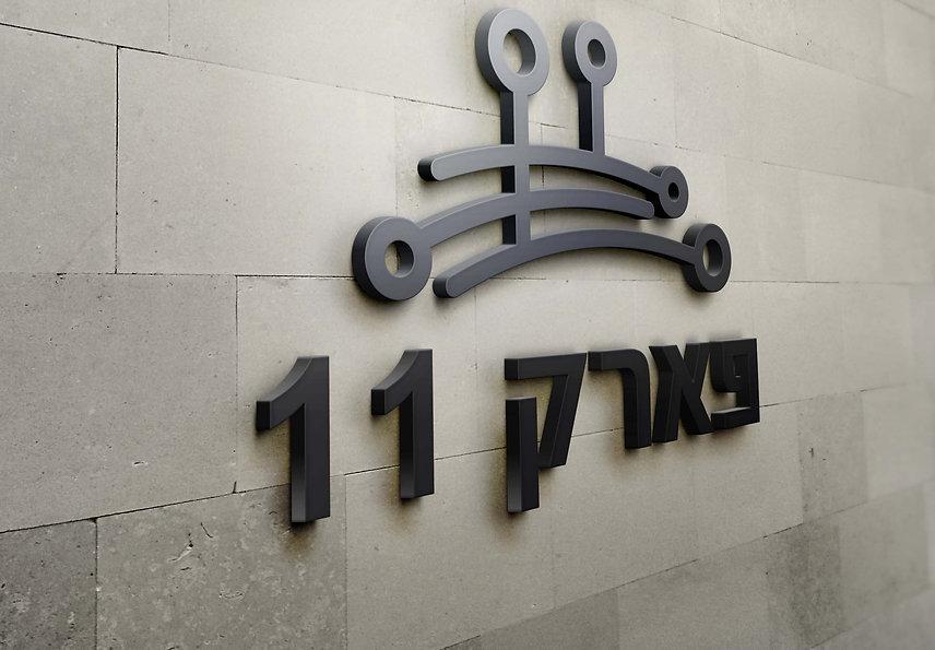 לוגו פארק 11 מבוצע במתכת על גבי קיר מחופה שיש.