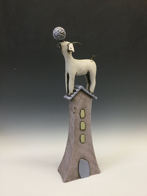 Large goat on house with ball