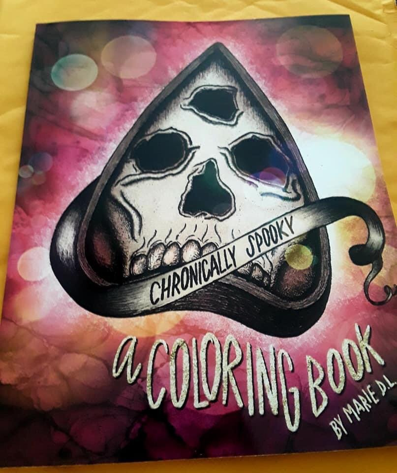 "The cover of chronically spooky; a hand drawn ouija planchette is in the center with a ribbon that wraps from behind with the words ""chronically spooky"" written on it. Underneath it in glitter hand lettering is ""a coloring book my Marie D.L."". Smoky galactic pink fills the background"