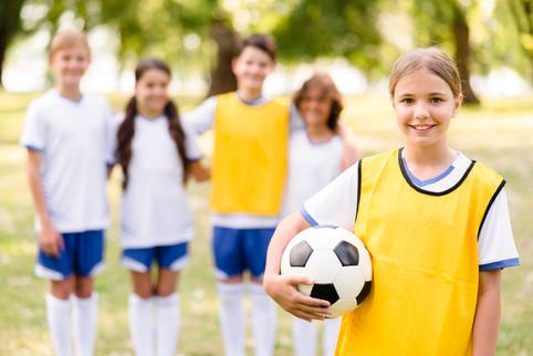 little-girl-holding-football-her-team-ma