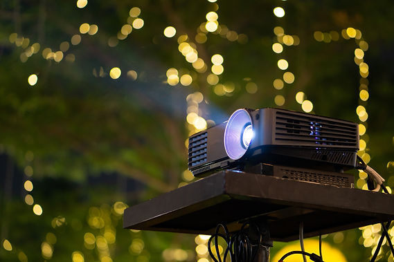 Black Projector on stand table ready for presentation in yellow bokeh background..jpg