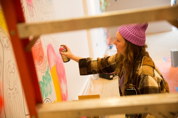 "Oakland artist Bud Snow works on her installation ""Many Places"" at Art Ventures gallery on Jan. 11, 2017. She says her work has been influenced by skateboard graphics and zines (small-circulation, self-published magazines or online publications). (Photo by Michelle Le/The Almanac.)"