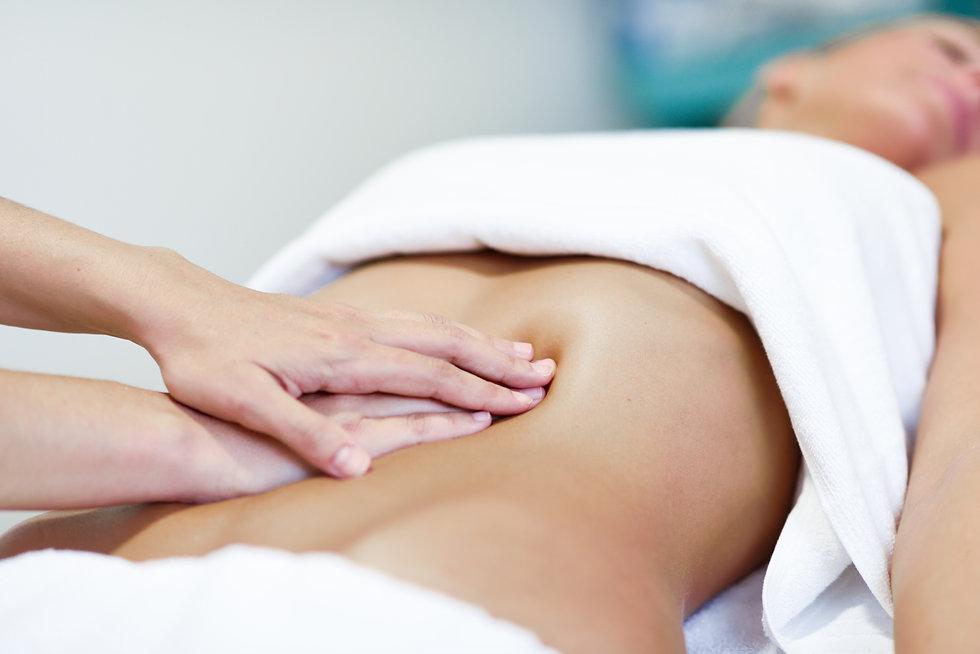 Hands massaging female abdomen.Therapist