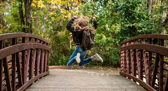 girl jumping on a wooden bridge