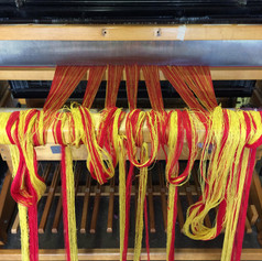 Rolling a new warp onto the loom