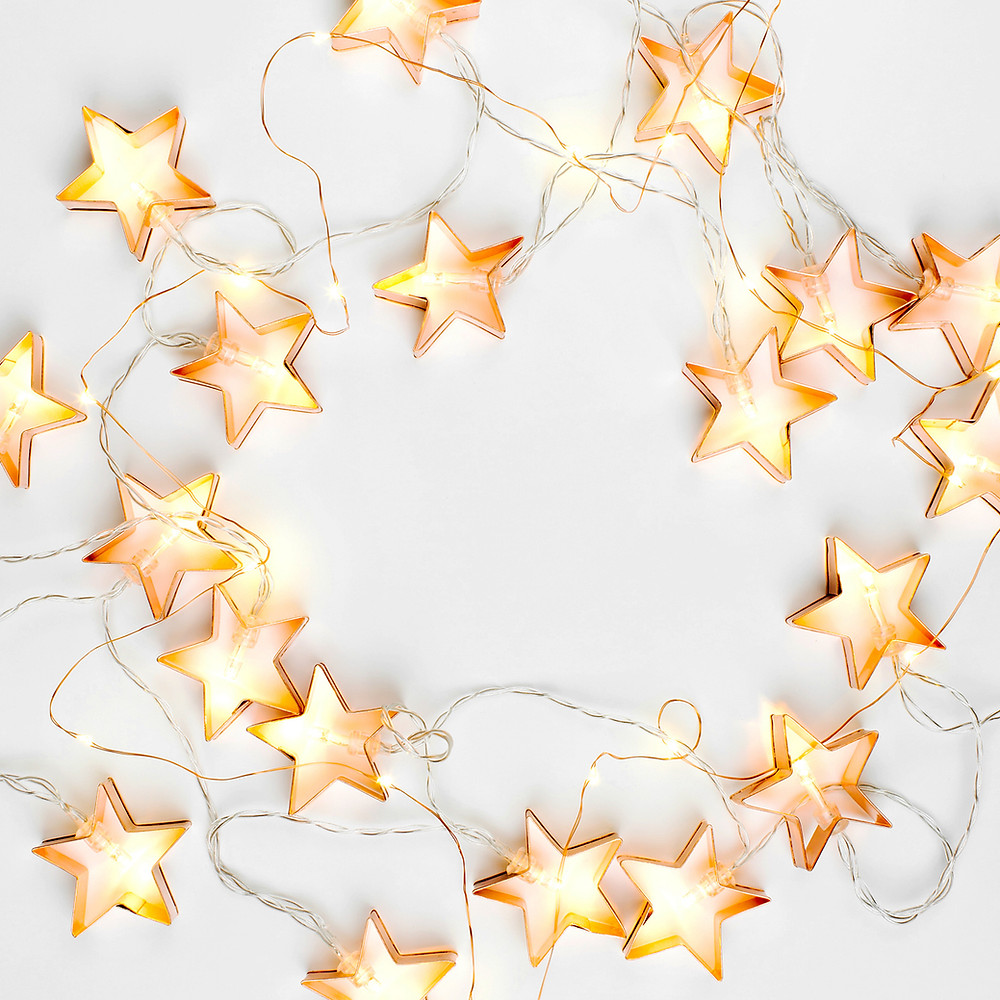 A string of yellow star lights laying on a white floor.