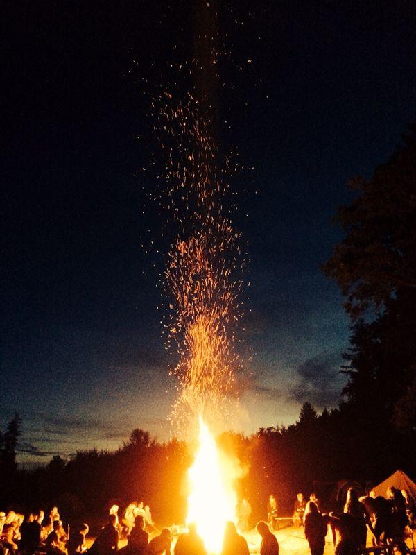 Gemütliches Lagerfeuer mit ein paar Leuten in einer warmen Sommernacht