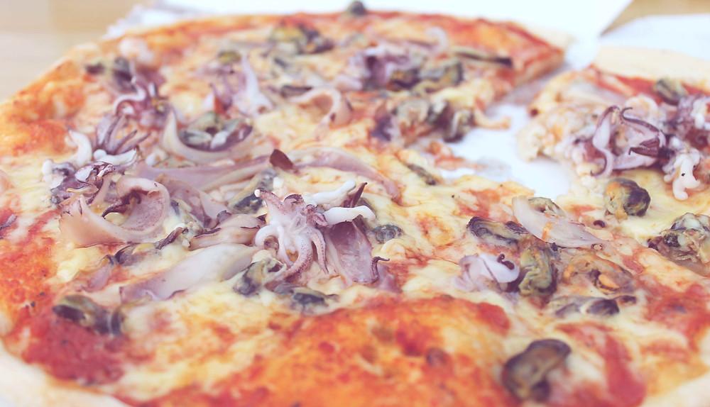 Pizza mit Zwiebeln und Meeresfrüchten