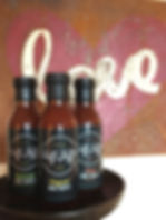 "Chef Jeff's BBQ sauce bottles lined up in front of a ""Love"" painting"