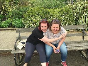 Steph and Vicky are sat on a bench. Steph has her arms around Vicky and they are both laughing.