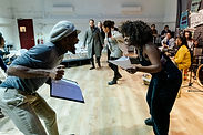 The Black Power Desk performers dancing and singing in a rehearsal room.