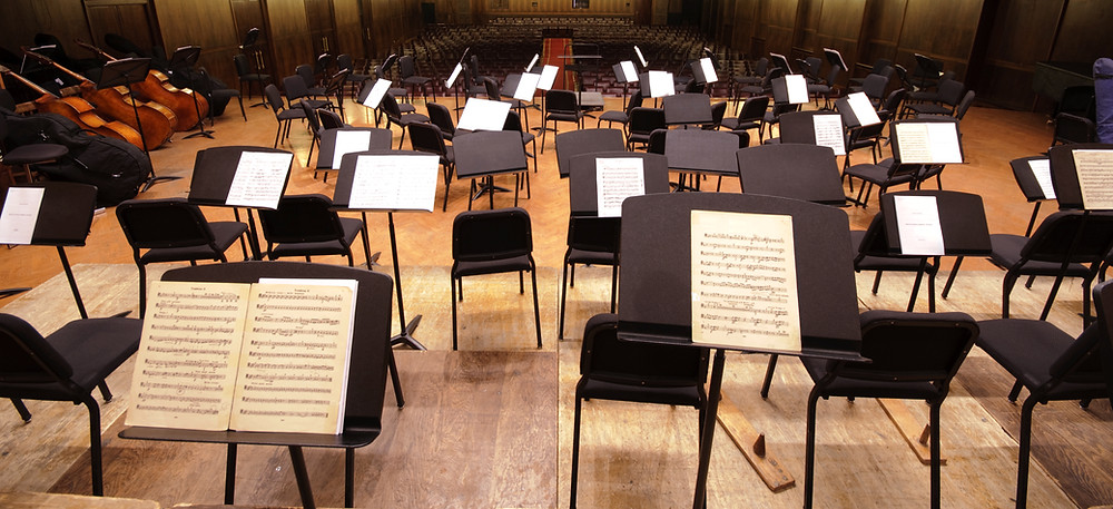 Empty stage filled with orchestra chairs and sheet music on pedestals