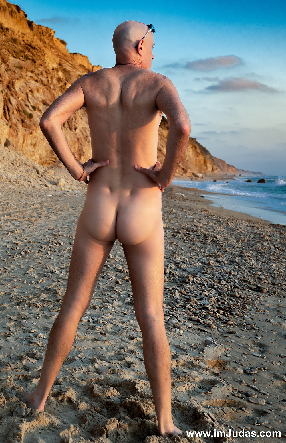 Standing naked at the beach