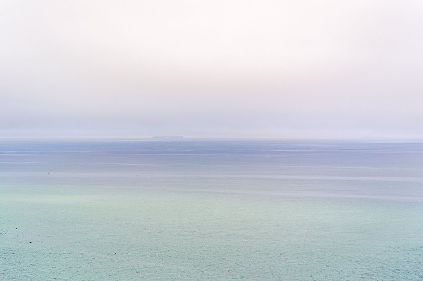 Soft-focus blue-tinted photo of beach and calm ocean beyond.