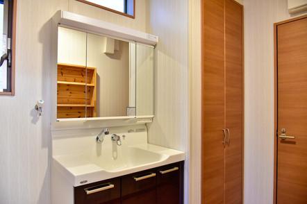 キッチンやカップボードとお揃いの洗面化粧台は人造大理石仕様で三面鏡付き